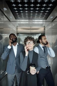 Gruppe von drei jungen interkulturellen büroleitern mit smartphones, die kunden im aufzug während der kaffeepause anrufen
