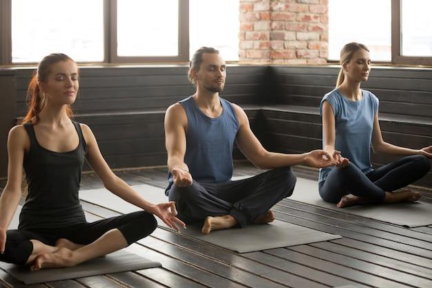Gruppe von drei jungen sportlichen leuten, die in sukhasana sitzen, werfen auf