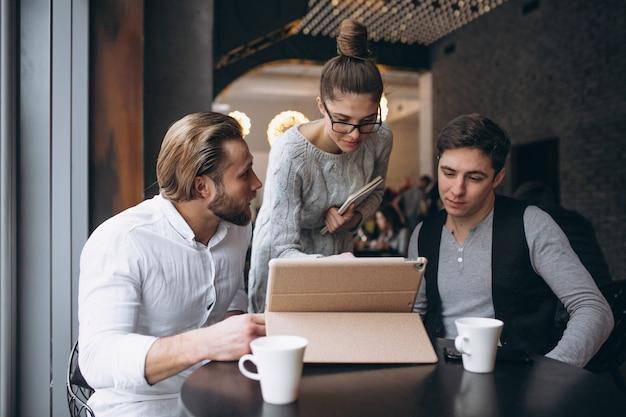 Gruppe von drei leuten, die an einem projekt auf einer tablette in einem café arbeiten
