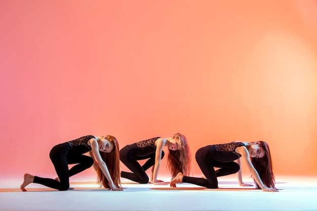 Gruppe von drei mädchen in schwarzen eng anliegenden anzügen, die auf einem roten hintergrund tanzen