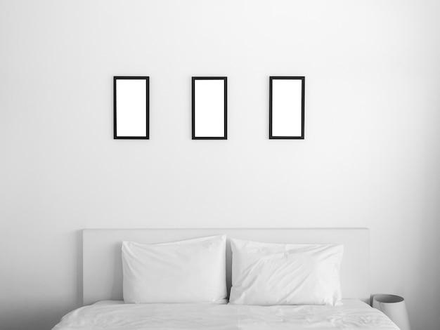 Gruppe von drei modellfotorahmen. weißes quadratisches bild mit schwarzem rahmenmodell, vertikaler stil, der am weißen wandhintergrund über dem bett im schlafzimmer hängt.