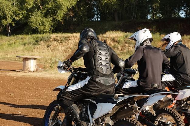 Gruppe von drei motorradfahrern in helmen, die auf motorrädern sitzen und sich auf das rennen über die offroad-strecke vorbereiten