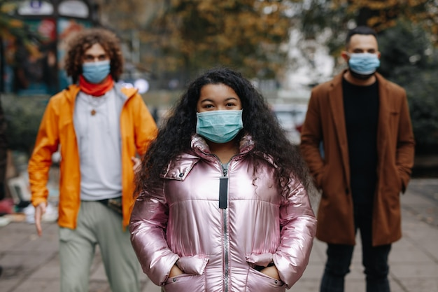 Gruppe von drei multikulturellen personen, die an der stadtstraße in medizinischen masken aufwerfen. konzept der sozialen distanz, quarantäne und maßnahmen.