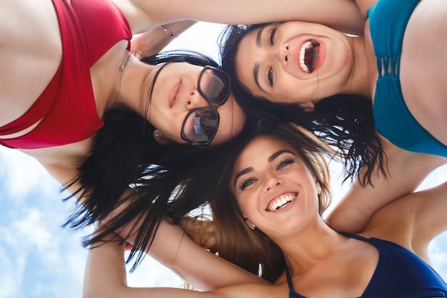 Gruppe von drei schönen jungen mädchen, die spaß am strand haben. nahaufnahmebild von fröhlichen frauen von unten. lächelnde gesellschaft