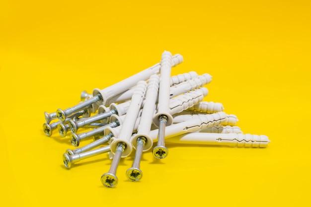 Gruppe von dübeln und nägeln auf gelbem hintergrund. dübel zur befestigung in beton. stock foto.