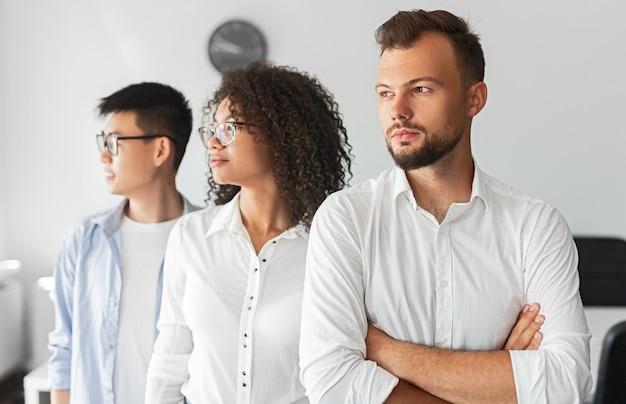 Gruppe von ernsthaften gemischtrassigen kollegen, die während der arbeit im modernen büro wegschauen