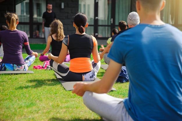 Gruppe von erwachsenen, die einen yoga-kurs draußen im hof besuchen