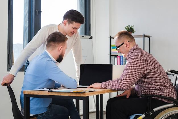 Gruppe von erwachsenen männern, die zusammen im büro arbeiten