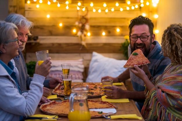 Gruppe von erwachsenen zusammen auf dem holztisch, die in der weihnachtsnacht zwei große pizzen isst - familie im freien beim abendessen