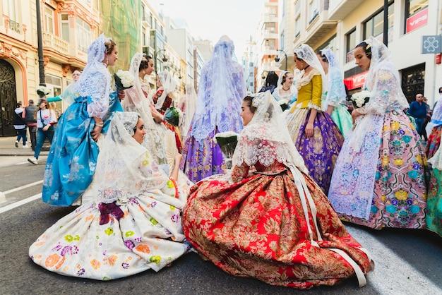 Gruppe von falleras und falleros, die in den straßen ruhen, während sie warten, um mit ihrem typisch spanischen kostüm vorzugehen.