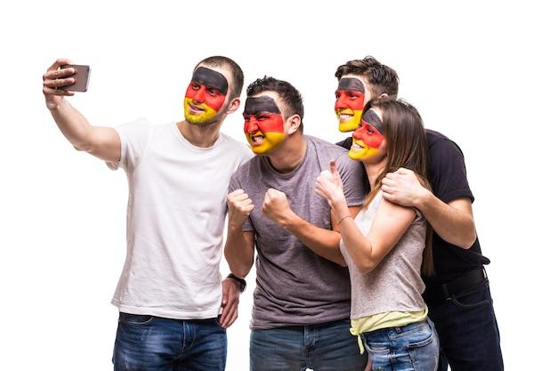 Gruppe von fans fans deutscher nationalmannschaften mit gemaltem flaggengesicht nehmen sefie vom telefon. fans emotionen.