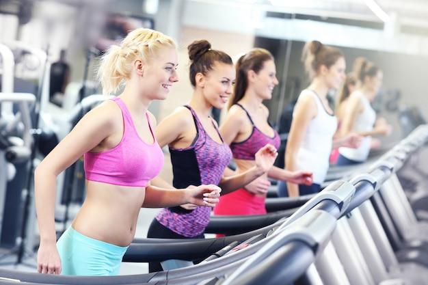 Gruppe von fitten frauen, die auf dem laufband im fitnessstudio trainieren