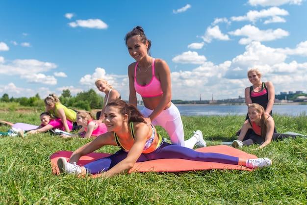 Gruppe von fitten mädchen, die trainieren, sich paarweise im freien dehnen.
