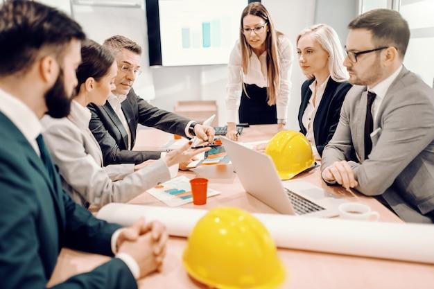 Gruppe von fleißigen architekten, die beim treffen sitzen und über großes projekt sprechen. die härteste arbeit der welt ist die, die gestern hätte geleistet werden sollen.
