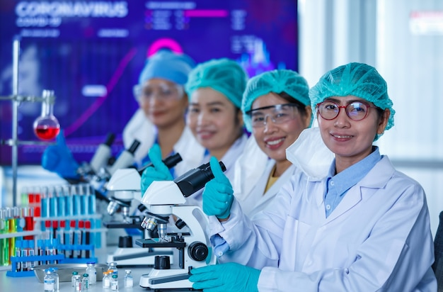 Gruppe von forscherinnen oder wissenschaftlern, die hygieneschutzmasken und medizinische uniformen tragen, zusammensitzen und mit mikroskopen und reagenzgläsern im labor arbeiten und in die kamera schauen.