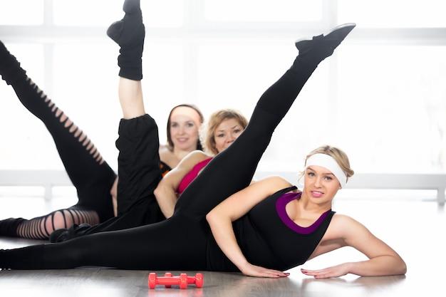 Gruppe von frauen, die aerobic-übungen im unterricht machen