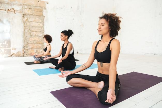 Gruppe von frauen, die auf einer yogamatte sitzen