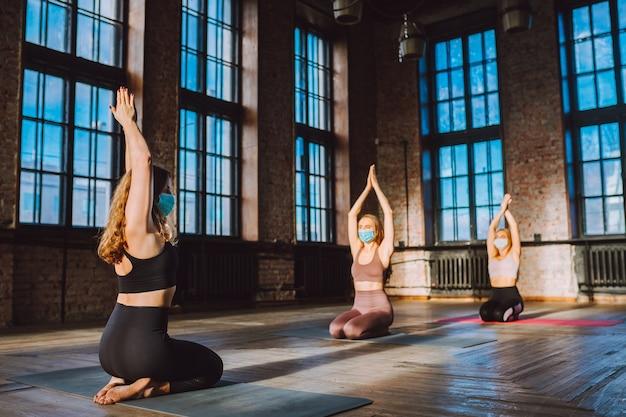 Gruppe von frauen, die yoga in der klasse des großen loftstils praktizieren, die schützende medizinische gesichtsmasken tragen. pandemie, soziales distanzkonzept.