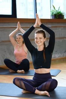 Gruppe von frauen, die yoga in halle machen.