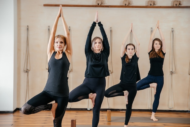 Gruppe von frauen, die yoga-stretching mit holzklötzen praktizieren, übung für wirbelsäule und schultern