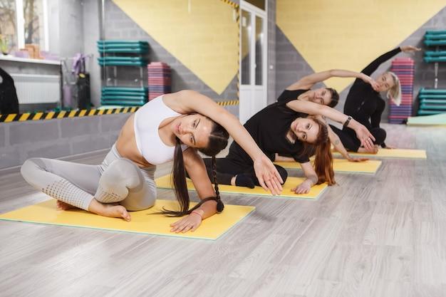 Gruppe von frauen, die zusammen im dehnstudio trainieren exercising