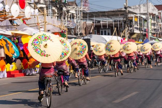 Gruppe von frauen in traditioneller tracht, die regenschirm hält und fahrrad fährt