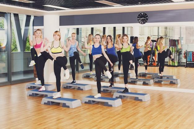 Gruppe von frauen, schritt aerobic im fitness-club