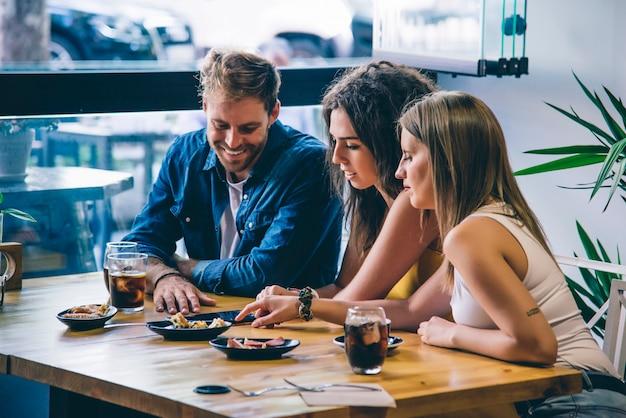 Gruppe von frauen und mann lächelnd, einen kaffee trinkend und smartphone verwendend