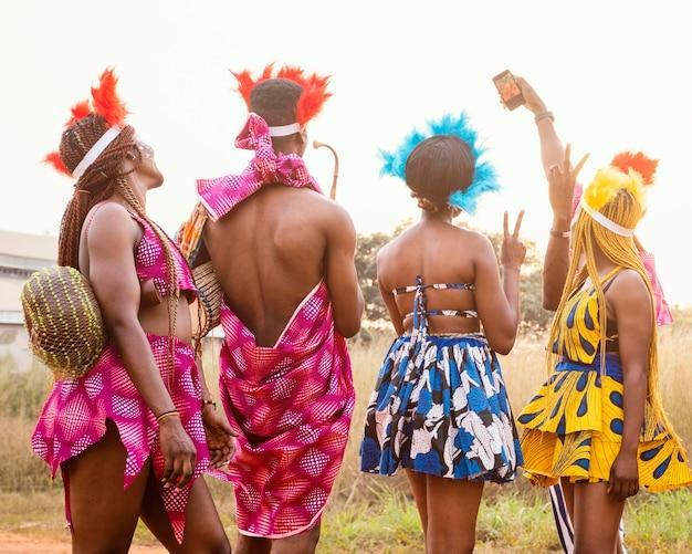 Gruppe von freunden am afrikanischen karneval, der kostüme trägt