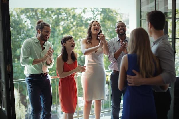 Gruppe von freunden applaudiert paar während der party