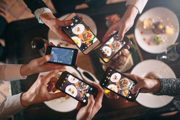 Gruppe von freunden ausgehen und ein foto von essen zusammen mit handy machen
