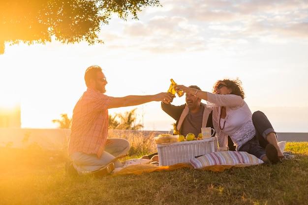 Gruppe von freunden bei freizeitaktivitäten im freien, die mit einigen bierflaschen klirren
