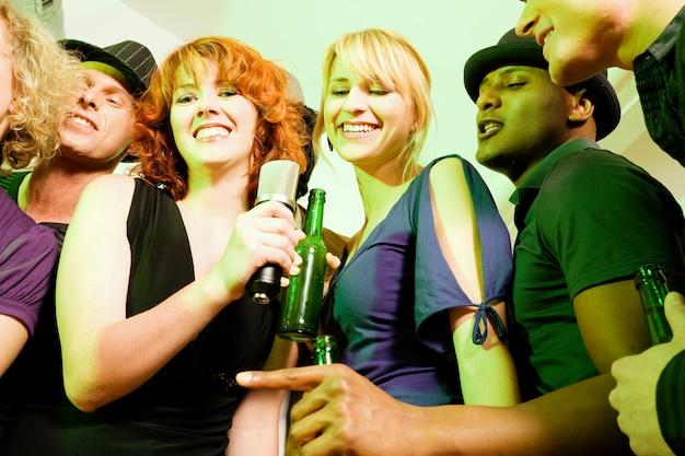 Gruppe von freunden bei karaoke-party