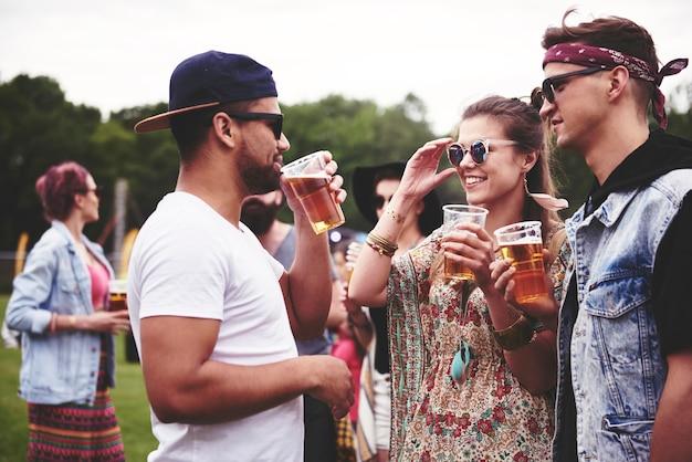 Gruppe von freunden beim biertrinken auf dem festival