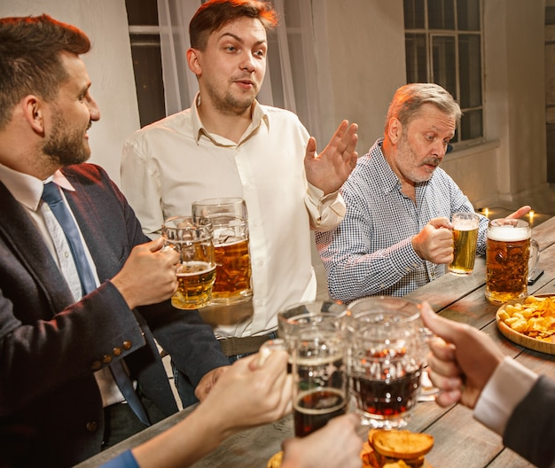 Gruppe von freunden, die abendgetränke mit bier genießen