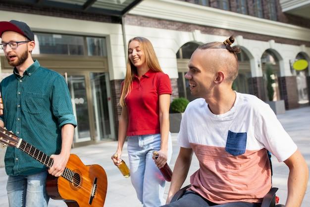 Gruppe von freunden, die am sommertag einen spaziergang auf der straße der stadt machen