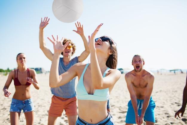 Gruppe von freunden, die am strandvolleyball am strand spielen