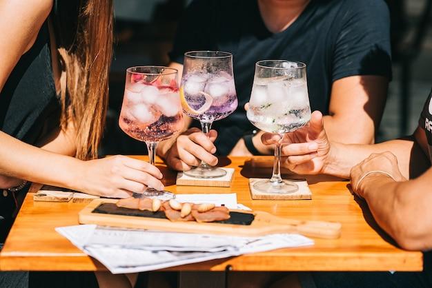 Gruppe von freunden, die auf der sommerterrasse sitzen und cocktails und snacks auf dem tisch halten