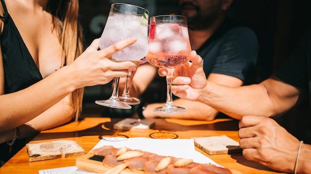 Gruppe von freunden, die auf der terrasse im sommer toast zusammen mit cocktails und einem snack sitzen