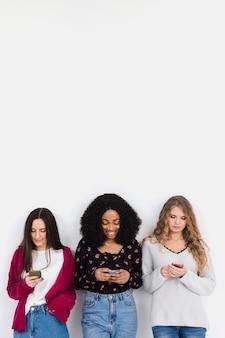 Gruppe von freunden, die auf einem telefon mit kopienraum suchen