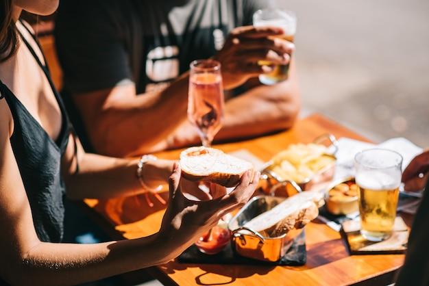 Gruppe von freunden, die auf einer sommerterrasse mit bier und champagner in ihren händen und snacks auf dem tisch sitzen