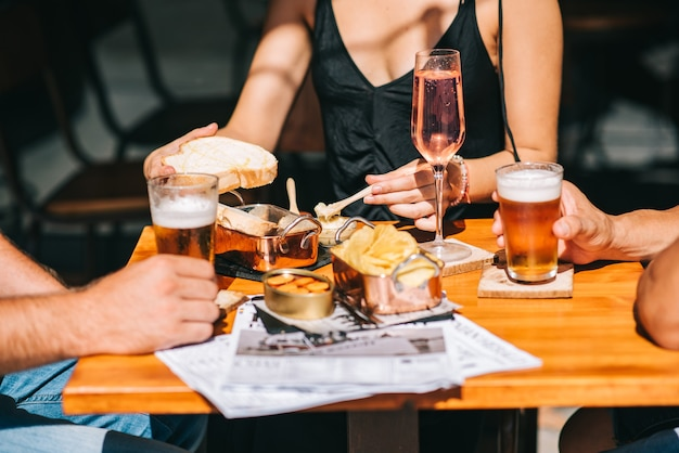 Gruppe von freunden, die auf einer sommerterrasse mit bier und wein in ihren händen und snacks auf dem tisch sitzen