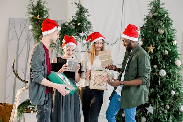 Gruppe von freunden, die auf weihnachtsfeier lachen und geschenke teilen