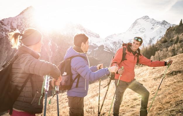 Gruppe von freunden, die bei sonnenuntergang auf den französischen alpen trekken