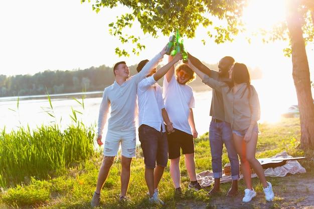Gruppe von freunden, die beim picknick am strand bierflaschen klirren.