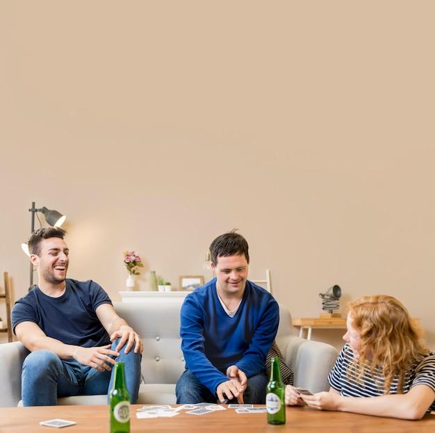 Gruppe von freunden, die bier und karten spielen
