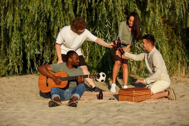 Gruppe von freunden, die bierflaschen während des picknicks am strand klirren. lebensstil, freundschaft, spaß, wochenende und ruhekonzept.