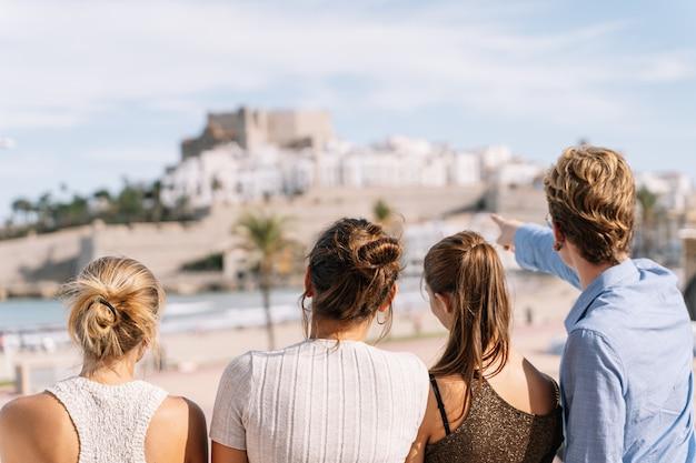 Gruppe von freunden, die die stadt peniscola während einer reise durch spanien betrachten