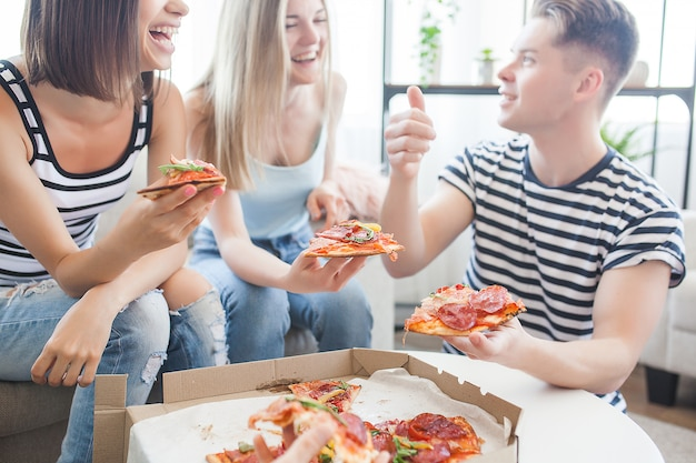 Gruppe von freunden, die drinnen pizza essen