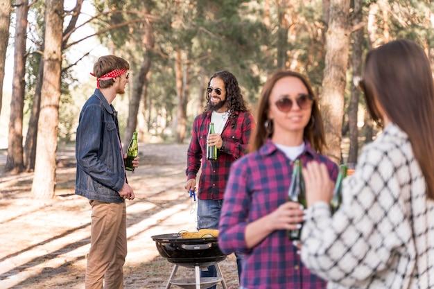 Gruppe von freunden, die einen grill mit bieren haben